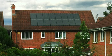 Man on roof installing PV Solar Panels
